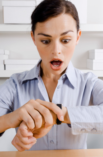 Gasping businesswoman looking at watch